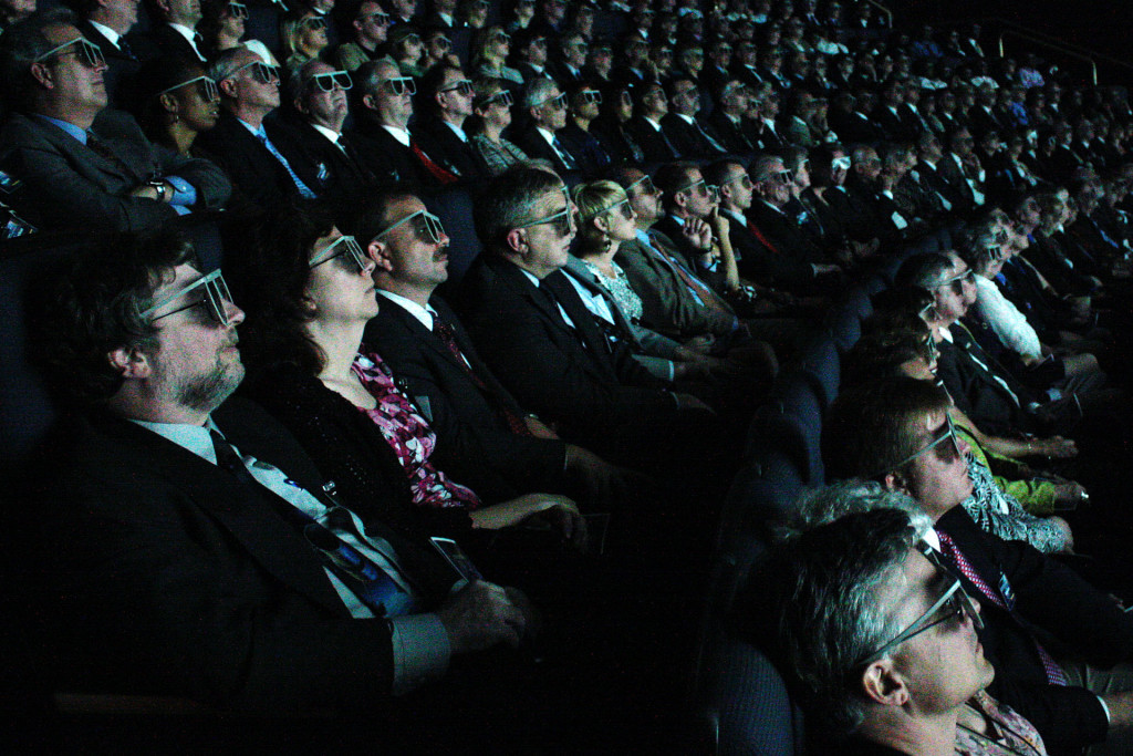 An IMAX audience watching the near-immersive supersized screen.